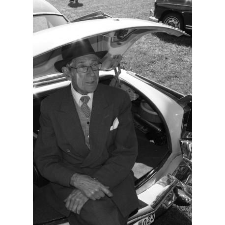 Fotokonst med poster på stilfull gentleman i sin Kaiser bil. Snyggt att blanda till en svartvit tavelvägg